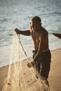 Man with fishing net in Com